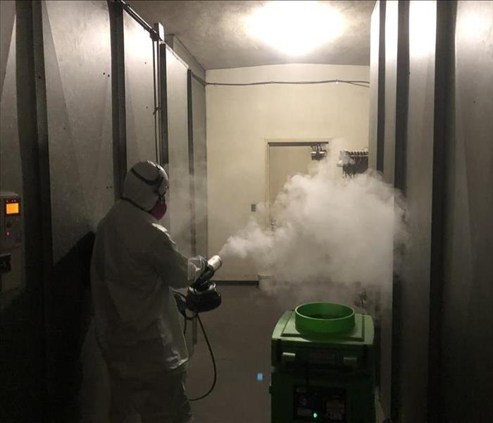 SERVPRO technician suited in PPE using a thermal fogger.