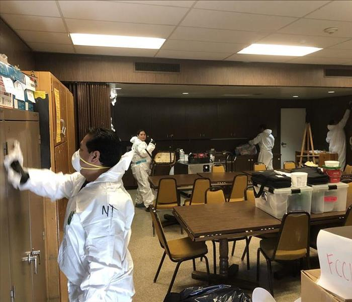 SERVPRO technicians suited in PPE clean a classroom.