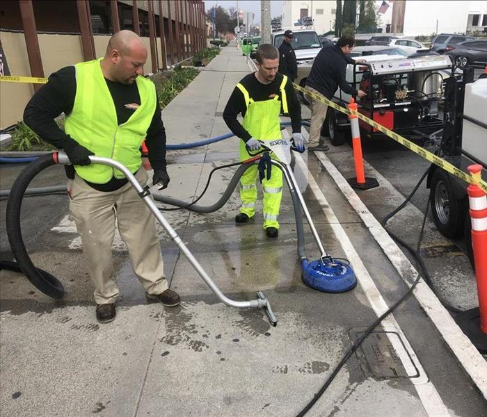2 SERVPRO technicians power washing sidewalk