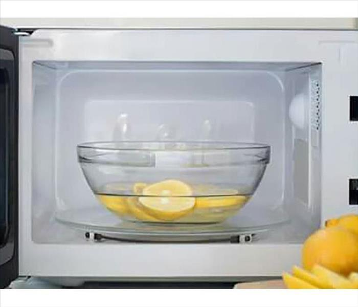 A bowl of water and lemons in the microwave